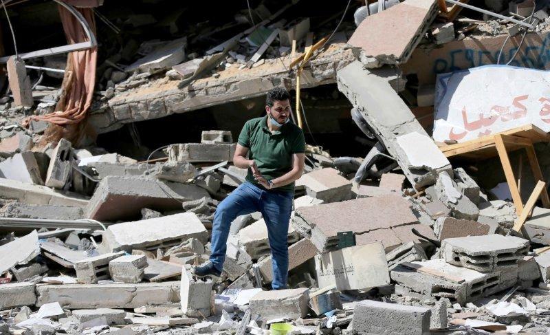 Warga Palestina Shaban Esleem berada di antara reruntuhan toko bukunya, yang hancur akibat serangan udara Israel selama pertempuran Israel-Palestina, di Kota Gaza, Senin (24/5/2021). Foto : REUTERS/Ibraheem Abu Mustafa.