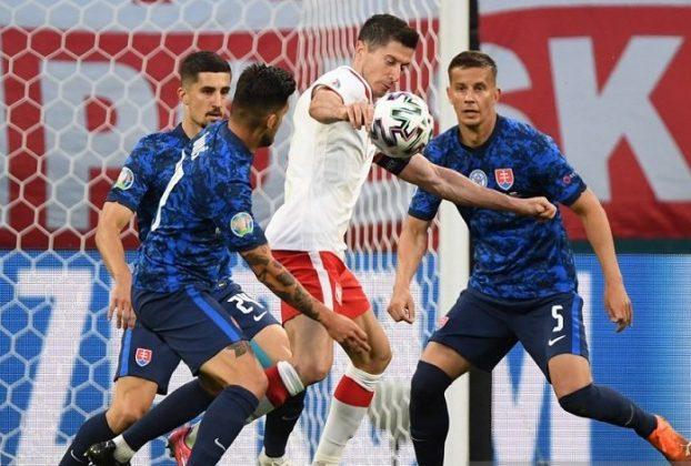 Penyerang tim nasional Polandia Robert Lewandowski dikawal ketat tiga pemain Slovakia dalam pertandingan pembuka Grup E Euro 2020 di Stadion Krestovsky, Saint Petersburg, Rusia, Senin (14/6/2021) waktu setempat. Foto : REUTERS.