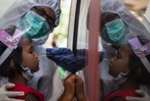 Seorang anak menjalani tes swab virus corona COVID-19. Foto : AFP.