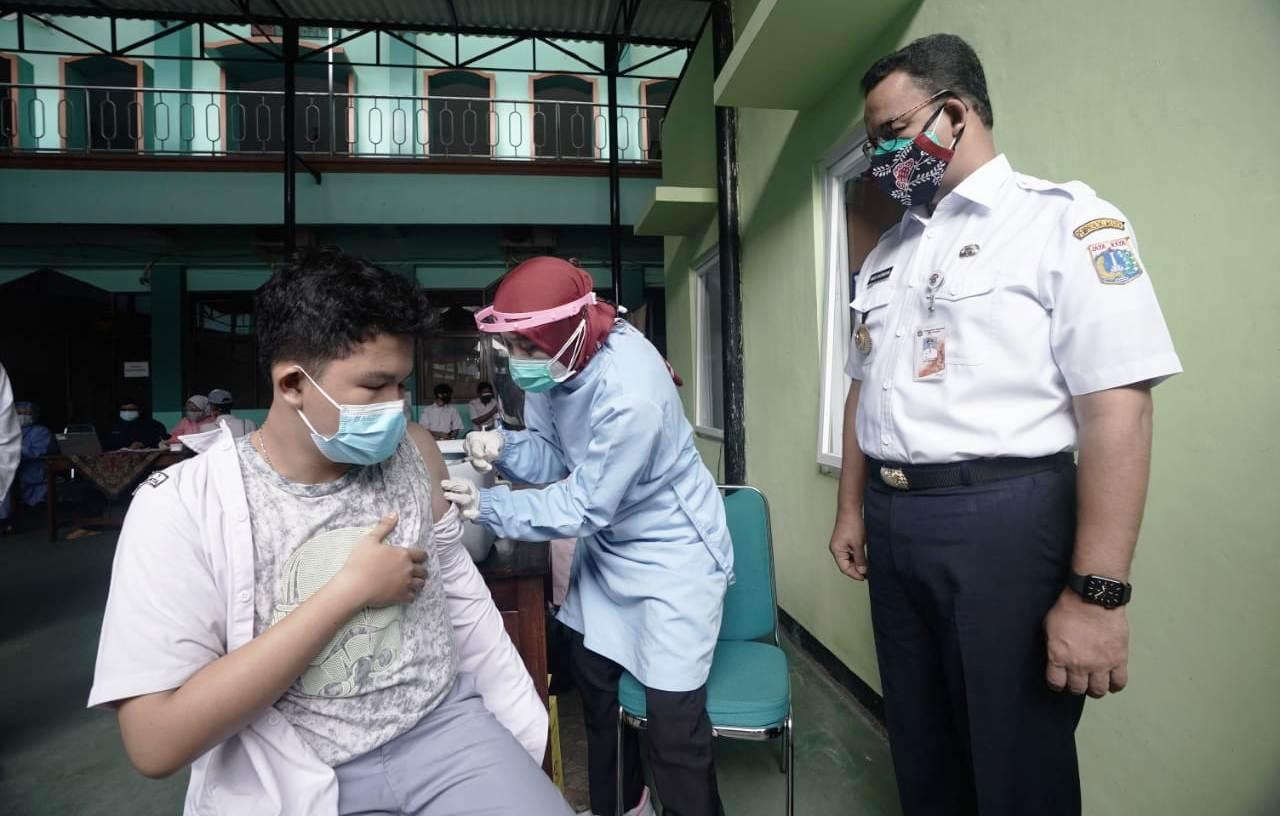 Didampingi Gubernur DKI Jakarta, Anies Baswedan, seorang pelajar tampak menerima suntikan vaksin covid-19 di salah satu sekolah di Jakarta.